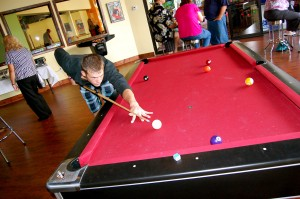 Guy shooting pool